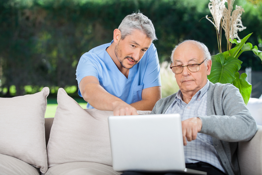Nurse Explaining Something On Laptop To Senior Man